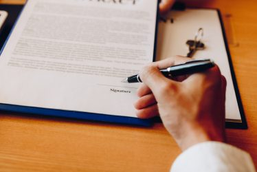 Hand client signing contract paper a real estate or mortgage contract.